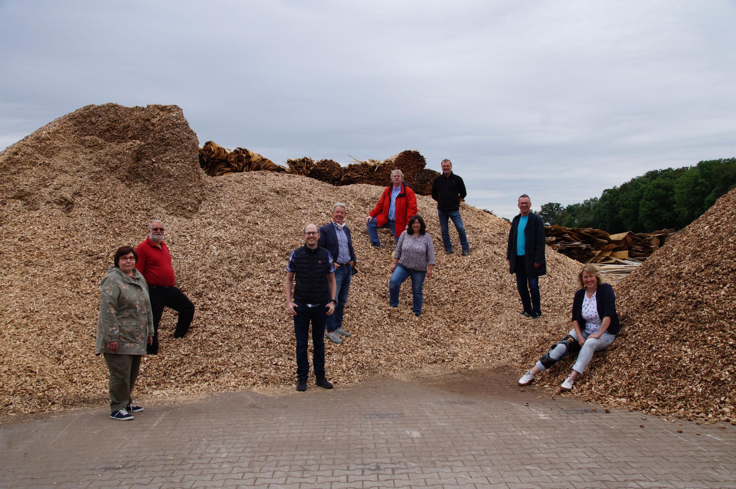 Menschen stehen auf einem Hügel aus Holzhackschnitzeln