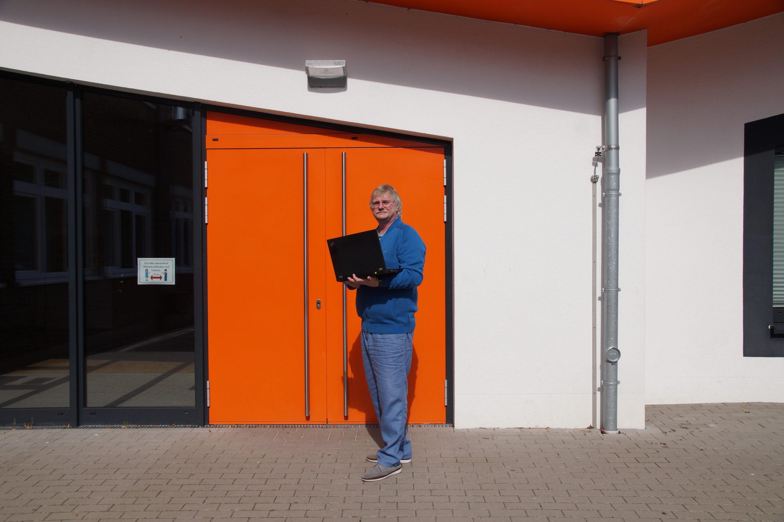 Dr.Wilfried Hamann mit Laptop vor der Grunschule Everswinkel.
