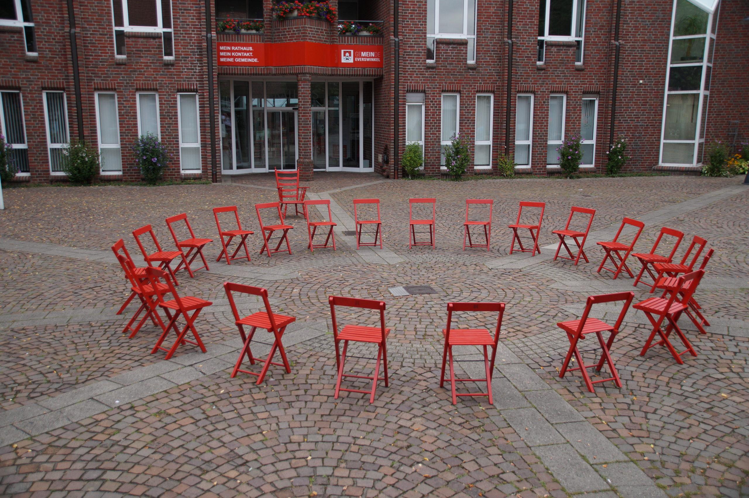 Stuhlkreis mit roten Stühlen vor dem Rathaus