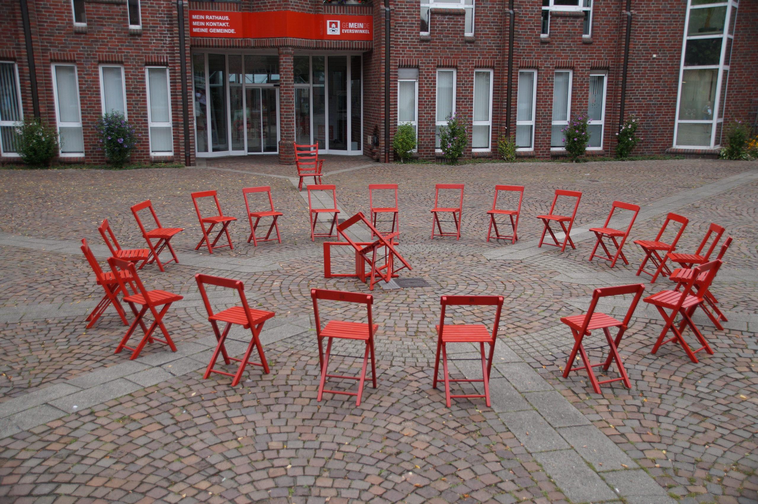 Ein Stuhlkreis aus roten Stühlen und in dern mit 3 umgestürzte Stühle