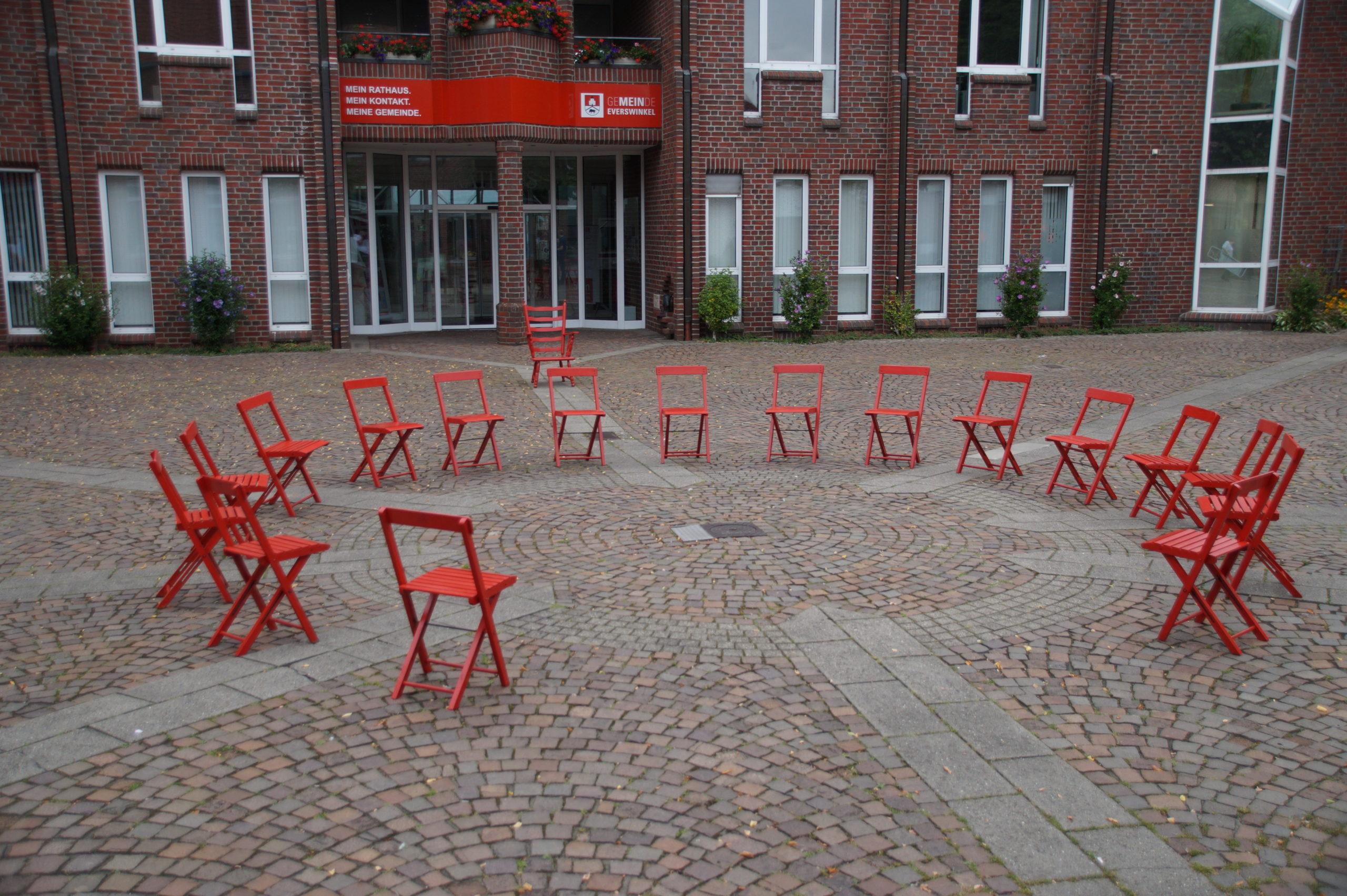 Ein roter Stuhlkreis mit offener Flanke