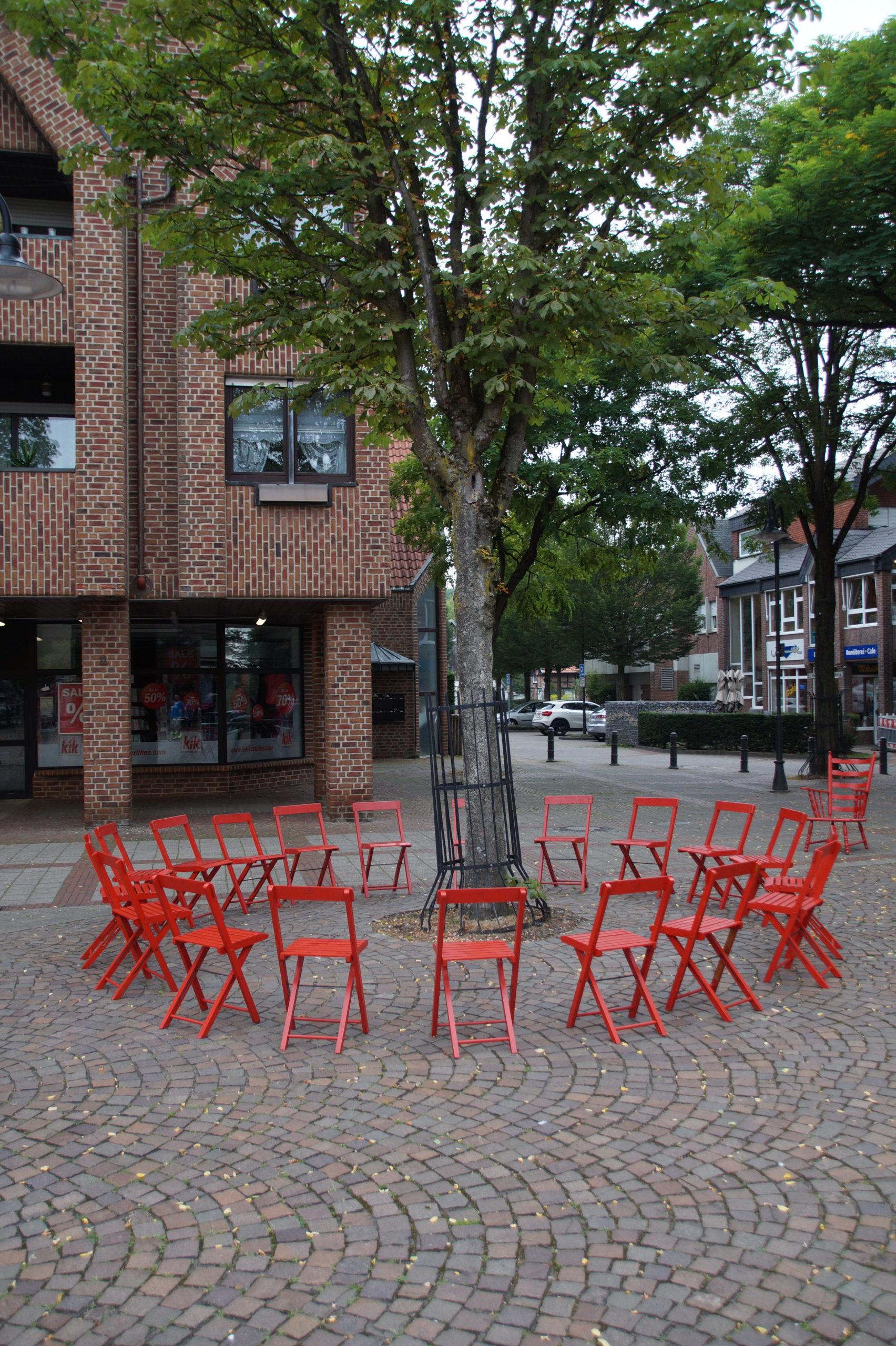 Rote Stühle im Kreis um einen Baum aufgestellt